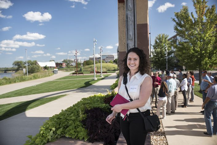 A woman stands in front of Cedar Rapids